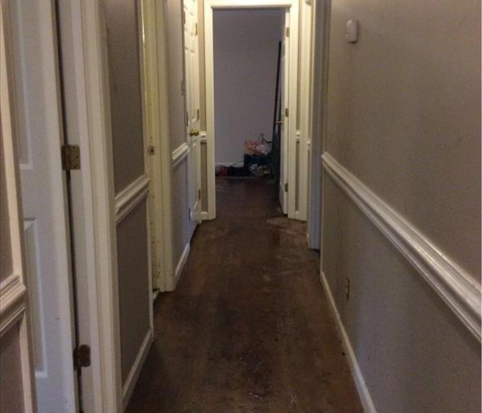 Water covered hardwood floors in hallway