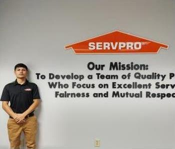Latino brown skin male with black hair wearing a SERVPRO logo polo shirt.