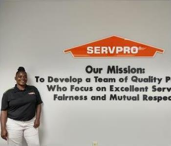 young black woman with black hair in a bun wearing a black SERVPRO polo.