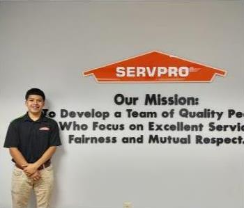 young latino male with black hair wearing a solid back SERVPRO logo t-shirt.