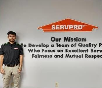 Latino brown skin male with black hair wearing a SERVPRO logo tee shirt.