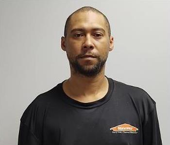 Brown skin black male with buzz cut and facial hair wearing a black SERVPRO logo tee shirt.