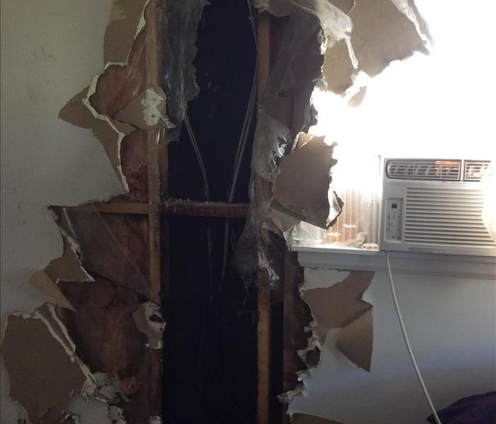 Fire left a gaping hole in the wall. Burned through sheetrock and down to the studs.