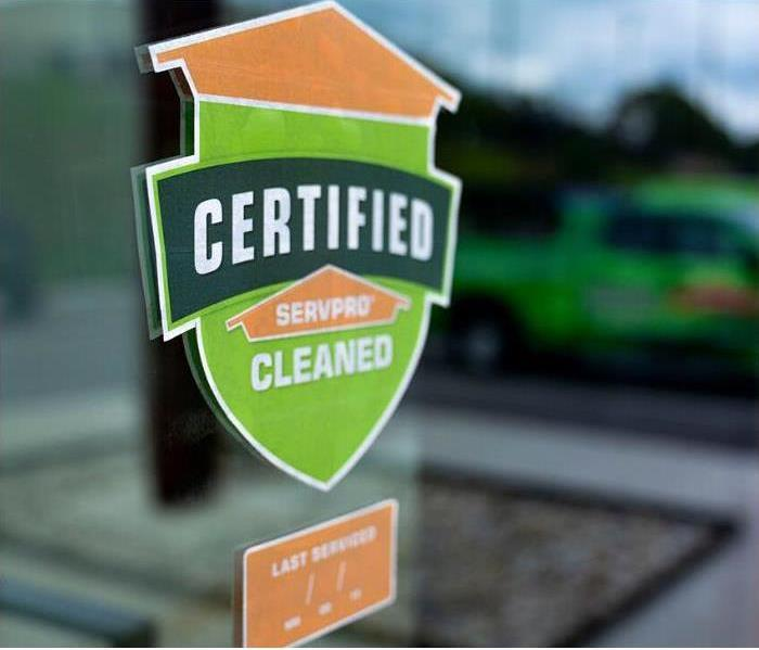 Certified: SERVPRO Cleaned green and organge graphic on the clear window of a business
