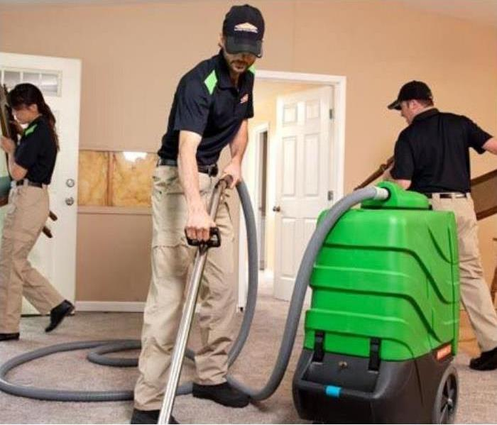 SERVPRO employees in company polo and khakis, wearing company hats, cleaning tan carpet with vacuum. door open on the left.
